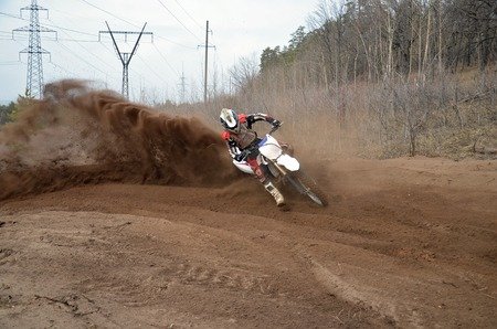 Motocross racer moves along sandy parapet turning track per motorcycle large plume of sand photo