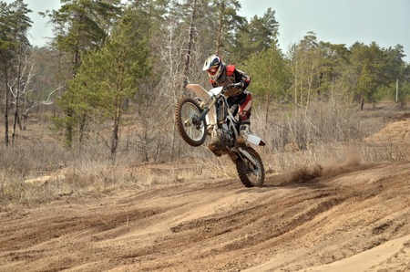 Motocross rider standing up in motion performed a wheelie on a sandy track