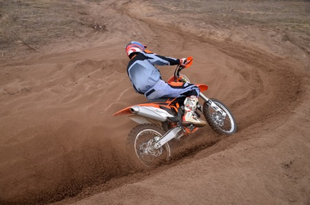 Entrance to the turning the sandy track of motocross racer with a slope of a motorcycle shot from behind