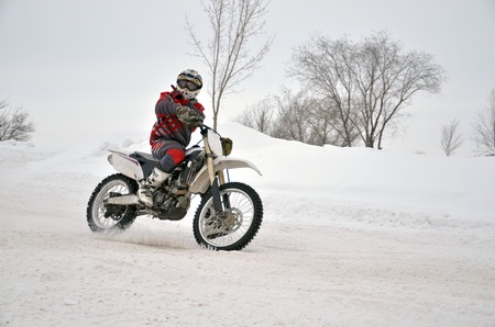 Motocross in winter left turn racer on a motorbike along the snowy track Stock Photo