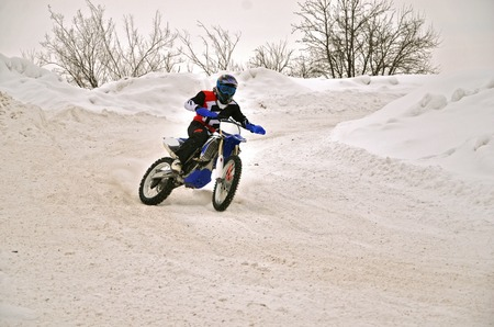 Motocross on snow racer on a motorcycle with a slope and a rear wheel skid Stock Photo