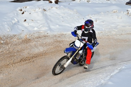 turnabout: Motocross in winter left turn racer on a motorbike along the snowy track Stock Photo