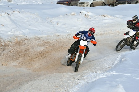 Winter MX, racer on a motorcycle rides with the demolition of the rear wheel on the snow-covered road in the reversal Stock Photo