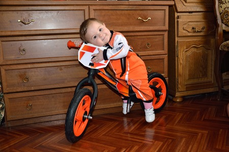 Child in orange his pajamas hugging the steering wheel sits on a balance bike