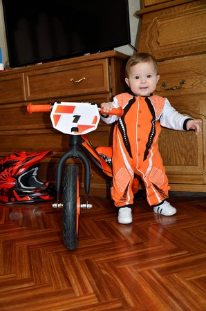 Little baby hands spread wide, standing next to a balance bike