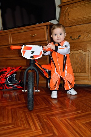 A child in the orange jumpsuit while standing holding the handlebars the small balance bike