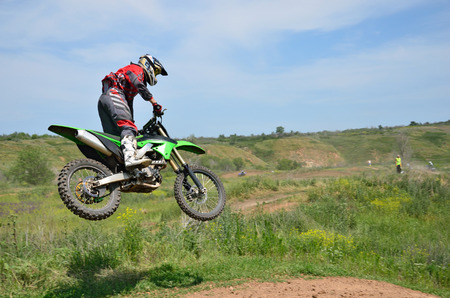 X Games rider standing on the motorcycle MX is flying over the hill on a background of blue sky