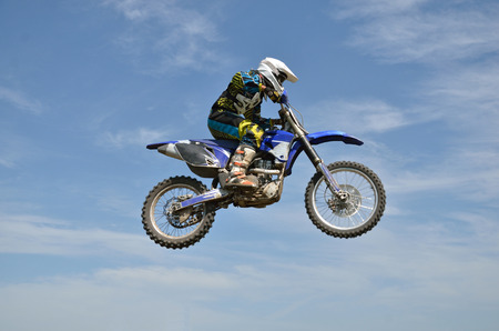 Motocross rider on the motorbike performs efficient flight is hanging in the open air against the blue sky