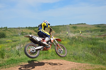 Motocross rider on a motorcycle is flying spectacularly in the last part of the flight  Stock Photo