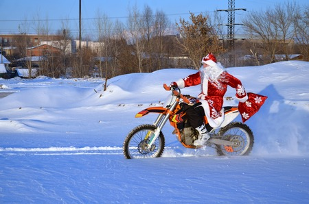 Santa Claus riding on a motocross bike in a red coat through the snow holds in a hand bag with gifts