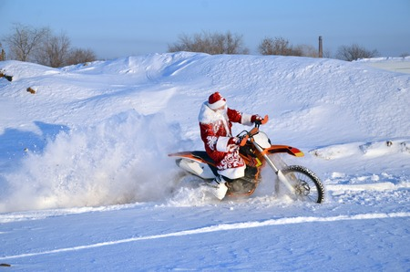 Santa Claus in a red coat and hat riding on the motocross bike on the background of a snowy field and village 写真素材
