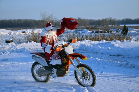 caftan: Extreme MX Santa Claus sitting on a motorcycle welcomes, lifting a bag of gifts on a background of snow and forests