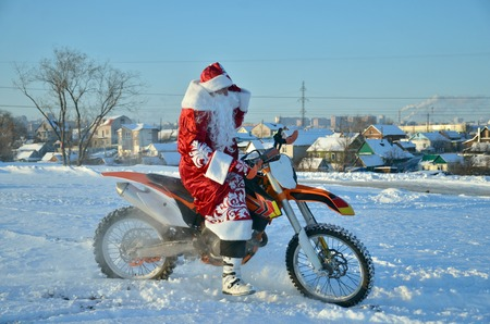 Santa Claus in a red coat and hat riding on the motocross bike on the background of a snowy field and village Stock Photo
