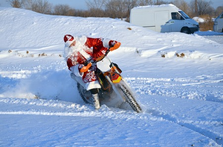 cornering: Santa Claus riding on a motorcycle MX through deep snow, cornering on the background of of snowdrifts