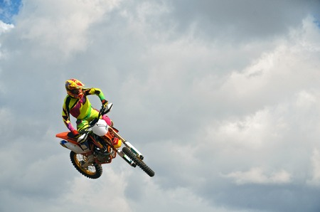 Motocross high jump MX racer on a motorcycle, on a background cloudy sky
