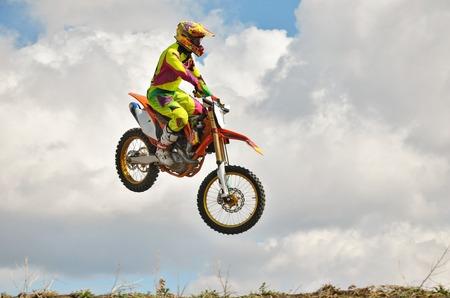 super cross: Jinete del motocr�s en una moto es volar espectacularmente en la �ltima parte del vuelo Foto de archivo