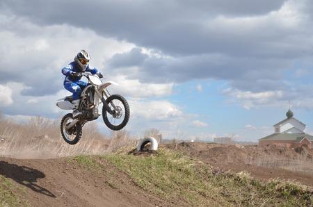 super cross: X Games jinete de pie sobre la moto MX est� volando sobre la colina sobre un fondo de cielo azul