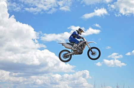 super cross: Jinete del motocr�s de pie sobre la moto MX est� volando sobre la colina sobre un fondo de cielo azul