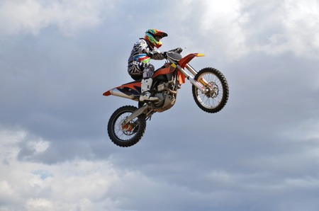 Motocross, a rider by motorcycle MX flies over the hill against the blue sky