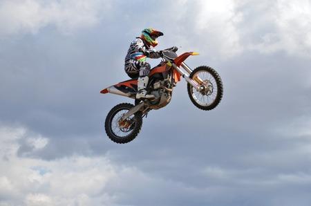 super cross: Motocross, un jinete en moto MX vuela sobre la colina contra el cielo azul