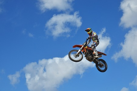 Motocross rider on the motorbike takes off from the hill ground has shifted back Stock Photo