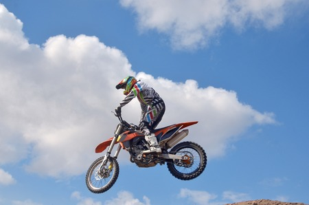 Extrem rider standing on the motorcycle MX is flying over the hill on a background of blue sky Stock Photo