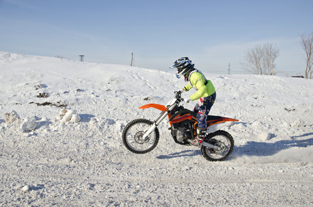 dispersed: Motocross winter, the driver is dispersed standing up on a motorcycle on the back wheel