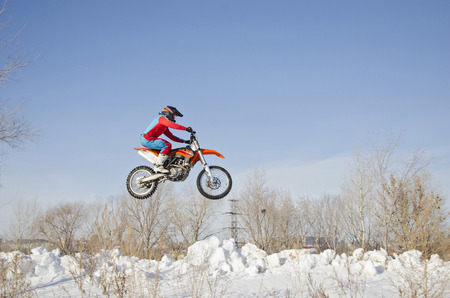 Winter Motocross rider stands on a motorcycle MX flies over a hill of snow against the blue sky