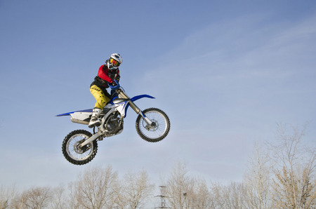 High jump extreme MX racer on a motorcycle, on a background cloudy sky Stock Photo