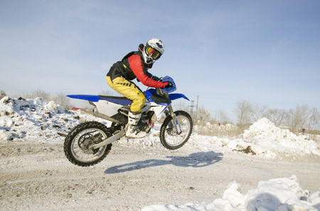 Motocross winter, a motorcycle racer flies up from the hill