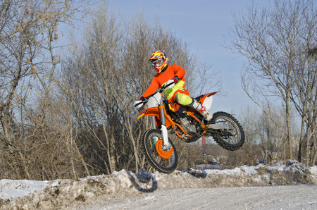 Motorcycling, the rider on the bike for motocross flies over the hill on a snowy highway