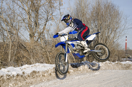 sidewards: Motocross in the winter, the rider by bike motocross flies sideways over a hill on a snowy road, shot from the left side