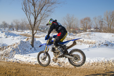 MX rider on a motorcycle flying against the backdrop of snowy hills