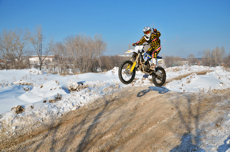 Motocross rider high in the air on a motorcycle one-hand control, against the backdrop of snowy hills Stock Photo