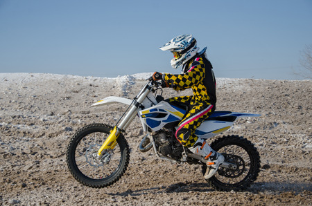 MX rider on a motorcycle starts to move on a snowy road with a raised front wheel Stock Photo