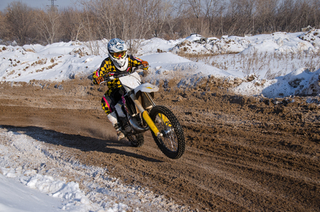 turnabout: MX racer turns the motorcycle is accelerated on snowy highway Stock Photo