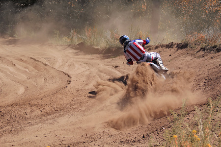 turnabout: Entrance to the turning the sandy track of motocross racer with a slope of a motorcycle shot from behind