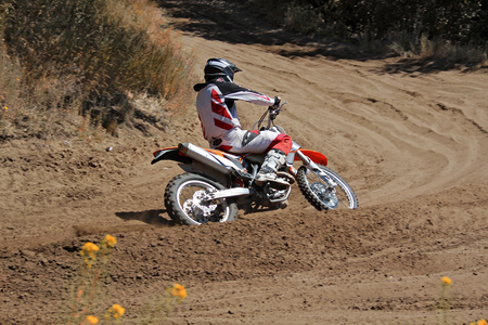 rides: MX rider on a motorcycle rides cornering along the sandy furrow motocross track