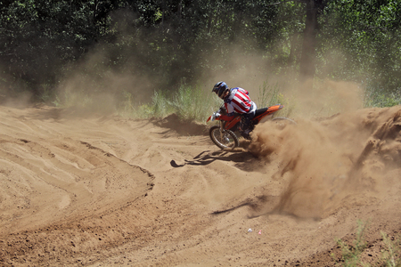 turnabout: MX the rider in the reversal on the sandy ruts with a large plume Stock Photo