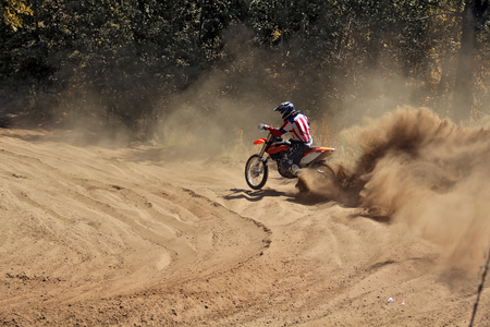 Motocross racer moves along sandy parapet turning track per motorcycle large plume of sand Stock Photo