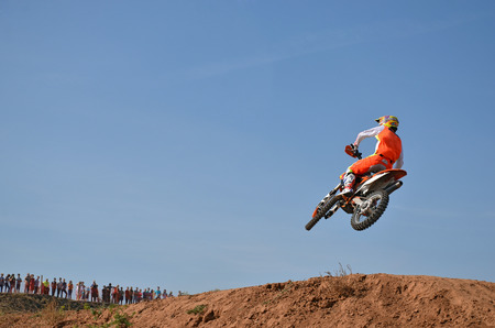 Leap over hill on a motorcycle on the background of blue sky, shot from behind Stock Photo