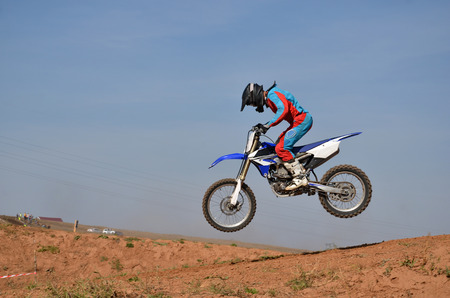 Motorcycle racer completes a jump, standing on a motorcycle motocross tilted forward Stock Photo