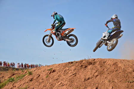 RUSSIA, SAMARA - SEPTEMBER 26: Two participants of motocross, 98 Bikteev I. 515 Nesytyh W., fly across the hill, the Regional Motocross on September 26, 2015 in Samara, Russia Editorial