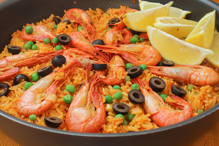 Mediterranean paella with shrimp, olives and green peas 免版税图像