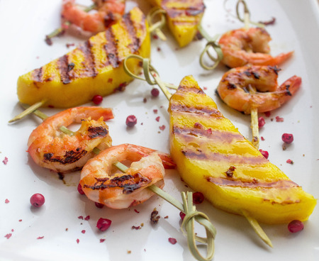 skewers of shrimp and mango with pink pepper