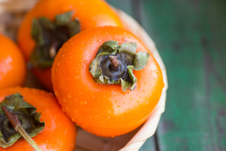 asia food: ripe persimmons in a wicker basket on the green boards Stock Photo