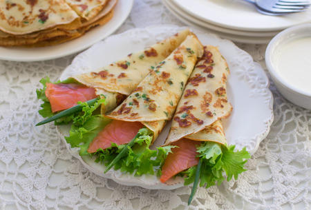 maslenitsa: Thin rolled pancakes, crepes with salmon, . Traditional Russian dish.