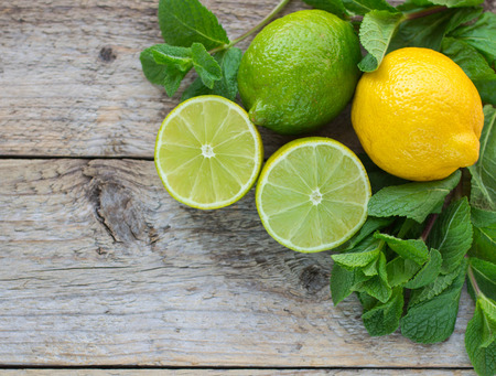 citruses: Juicy ripe citrus on an old wooden table - lime, lemon and mint Stock Photo