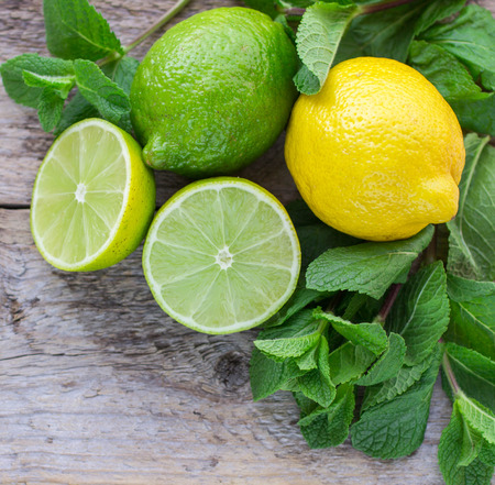 Juicy ripe citrus on an old wooden table - lime, lemon and mint Stockfoto