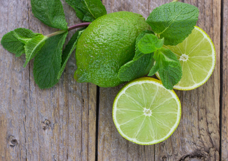 Juicy ripe limes and mint on wooden table Stockfoto